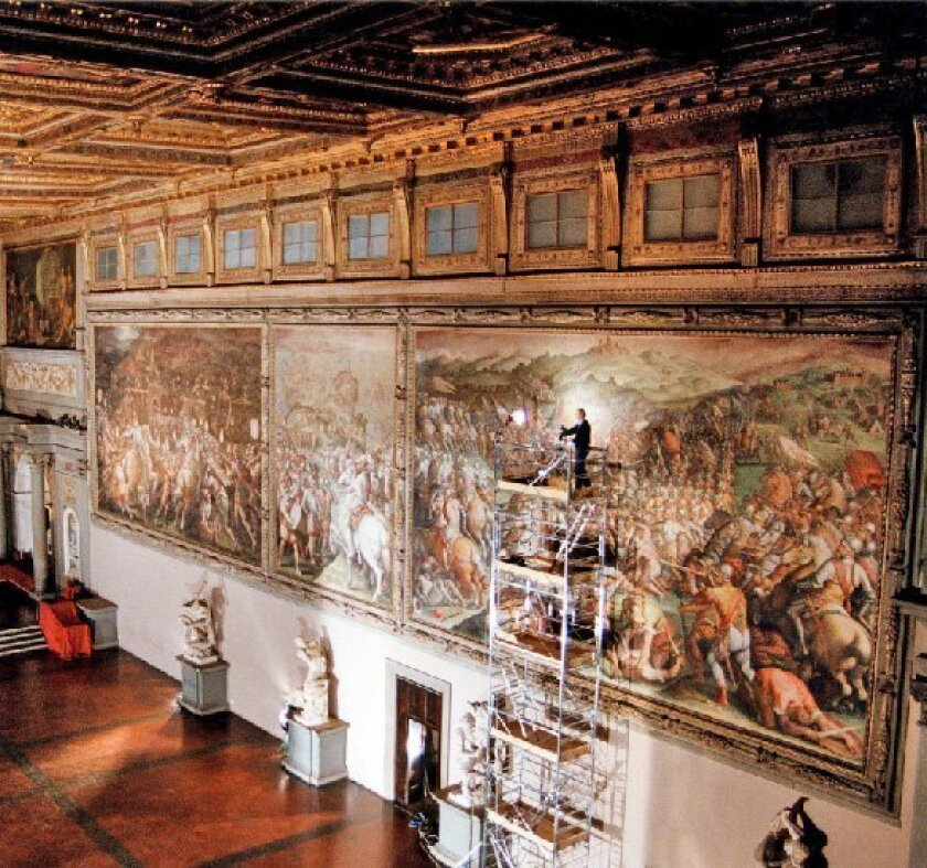 Maurizio Seracini of UCSD stands atop scaffolding in the Hall of 500 in Florence's Palazzo Vecchio, studying a giant mural by 16th century artist Giorgio Vasari. (New York Times)