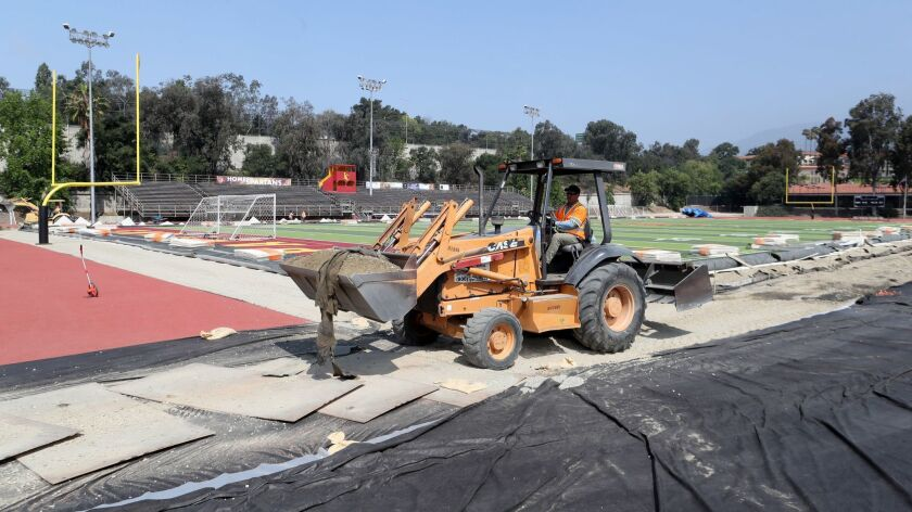 Dump trucks and heavy machinery remove loads of rock from the drainage area of the football field at