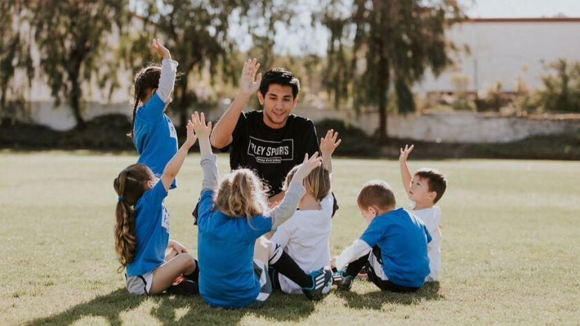 Pley Sports founder John Leal, 26 of Vista, shares high fives with preschool-age soccer students.