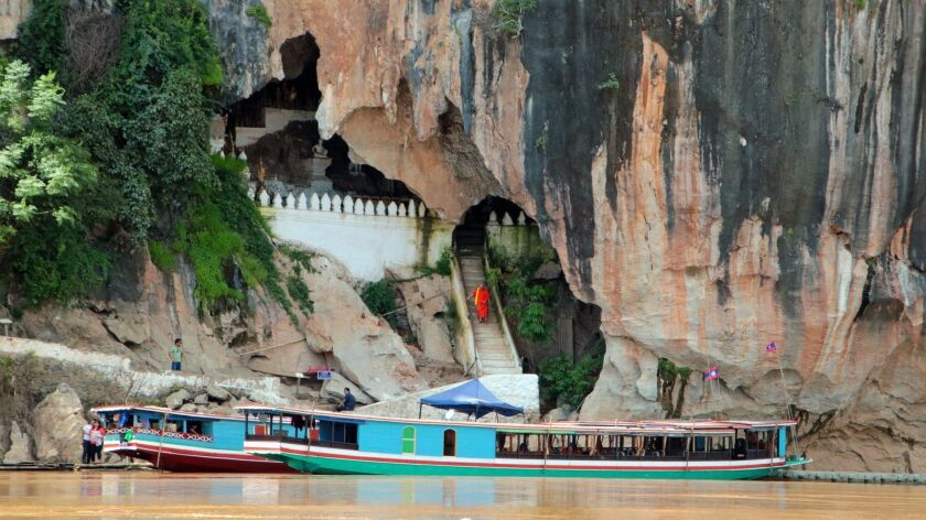 A monk descends from the Pak Ou Caves, a historic holy site crammed with hundreds of Buddha statuett
