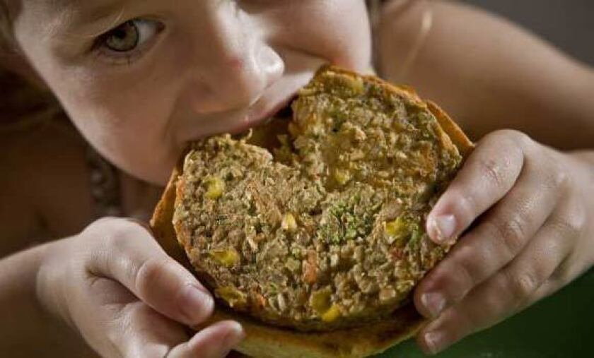 A child eats a garden burger from Whole Foods Market.
