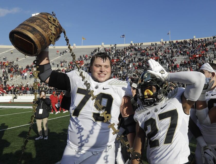 FILE - Purdue's Matt McCann (79) and Navon Mosley (27) celebrates with the Old Oaken Bucket after Purdue defeated Indiana in an NCAA college football game in Bloomington, Ind., in this Saturday, Nov. 24, 2018, file photo. The Indiana-Purdue rivalry game has been canceled again. It will be the first time in-state rivals have not met in a football season since the Spanish flu pandemic forced cancellations in 1918 and '19.(Darron Cummings, File)