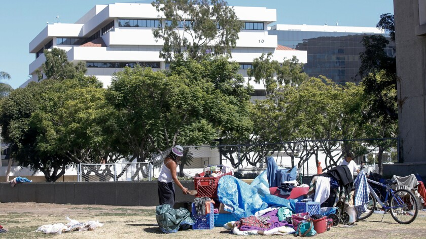 With the Orange County Hall Of Administration in the background, a homeless encampment thrives on the dead grass in the Santa Ana Civic Center Plaza.