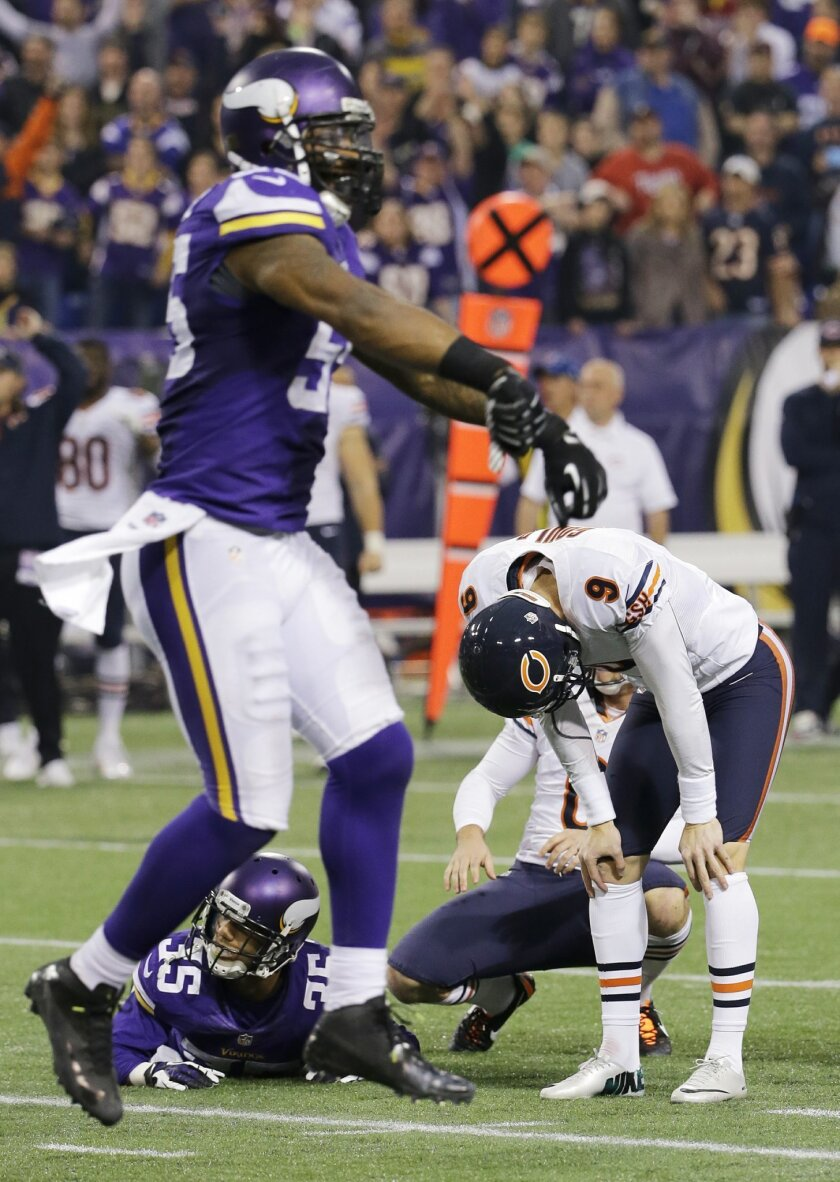 Chicago Bears kicker Robbie Gould (9) reacts in front of Minnesota Vikings defenders Marcus Sherels (35) and Marvin Mitchell after missing a field goal during overtime of an NFL football game on Sunday, Dec. 1, 2013, in Minneapolis. The Vikings won 23-20. (AP Photo/Ann Heisenfelt)