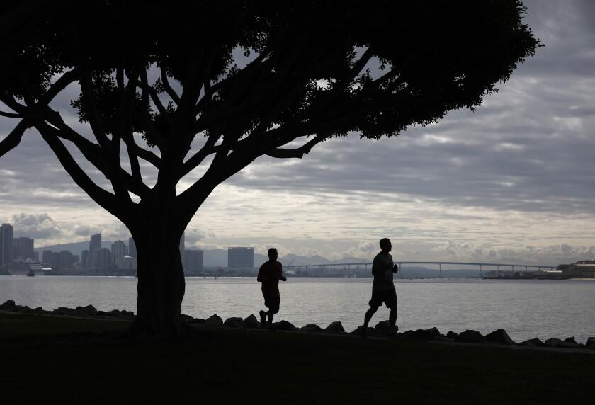 Runners run along Harbor Island.