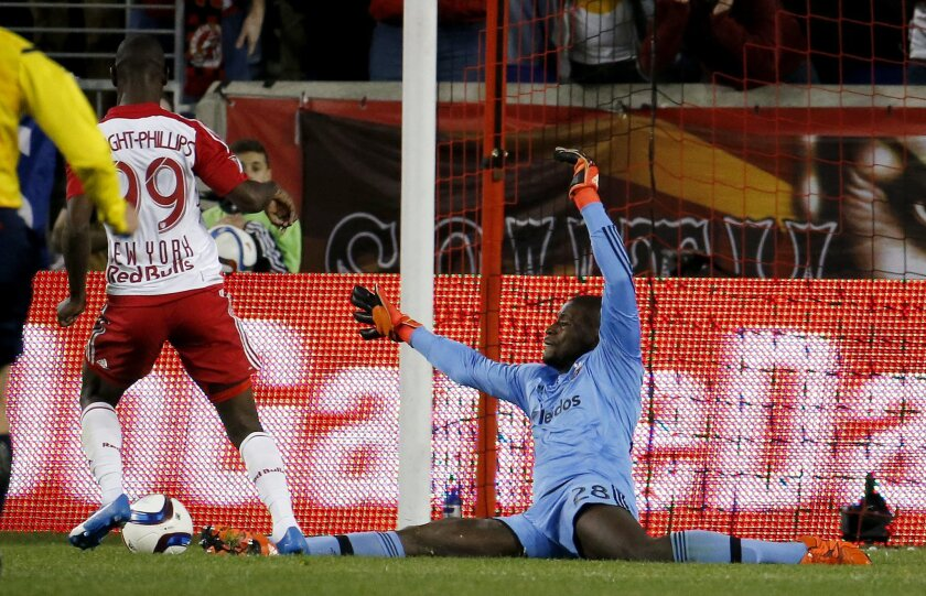 New York Red Bulls forward Bradley Wright-Phillips (99) beats D.C. United goalkeeper Bill Hamid before scoring a goal during the second half of an MLS playoff soccer match, Sunday, Nov. 8, 2015, in Harrison, N.J. The Red Bulls won 1-0. (AP Photo/Julio Cortez)