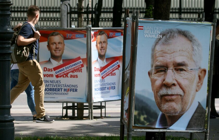 People walk between election posters of Alexander Van der Bellen, candidate for presidential elections and former head of the Austrian Greens, right, and Norbert Hofer, candidate for presidential elections of Austria's right-wing Freedom Party, FPOE, left, in Vienna, Austria, Monday, May 23, 2016. The Eurosceptic, anti-immigration right-winger Norbert Hofer, and his left-leaning rival are neck and neck in Austria's presidential election a day after polls closed, and officials are now counting absentee ballots to determine who will win. (AP Photo/Ronald Zak) (AP Photo/Ronald Zak)