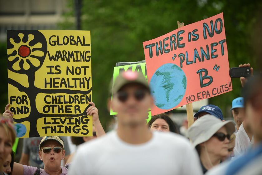 Protesters rally against the Trump administration's environmental policies, which they say abandon the fight against climate change.