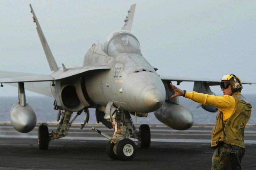 FILE-This April 7, 2003 file photo a deck crew member of the USS Carl Vinson guides an F/A-18C Hornet during a take-off and landing exercise of fighter jets during the aircraft carrier's operation off the western Pacific Ocean. Two U.S. Navy jets similar to the one pictured crashed into the western