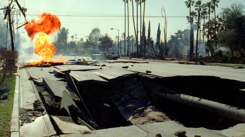 Ruptured gas mains burn behind a giant crater in the 11600 block of Balboa Boulevard in Granada Hills on Jan. 17, 1994, after the Northridge earthquake. Several homes burned near where the gas line exploded.