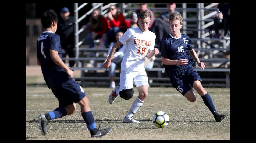 Flintridge Prep soccer player #16 Jason Krienberg battles for the ball with La Canada High School player #18 Matthew Brown in home game in La Canada Flintridge on Saturday Dec. 22, 2018. Game ended tied 1-1.