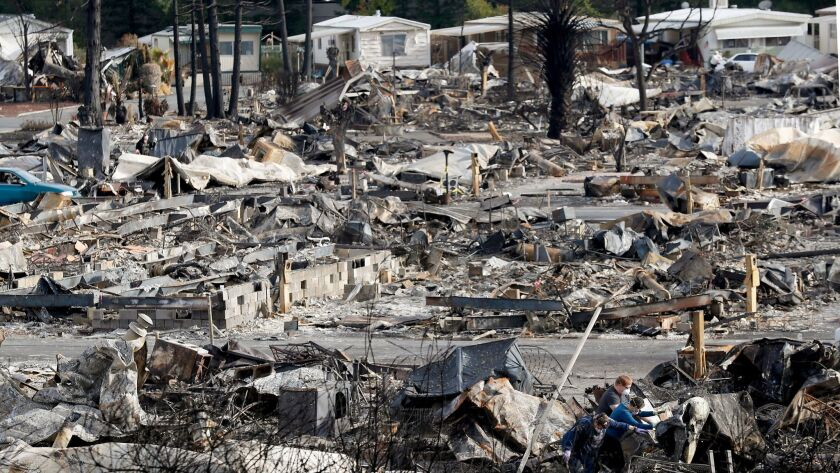 Police in Santa Rosa, Calif., arrested two suspects after a high-speed chase through city streets along the southern edge of destruction where the Tubbs Fire had burned. Residents, above, clear away debris from neighborhood damaged by the firestorm.