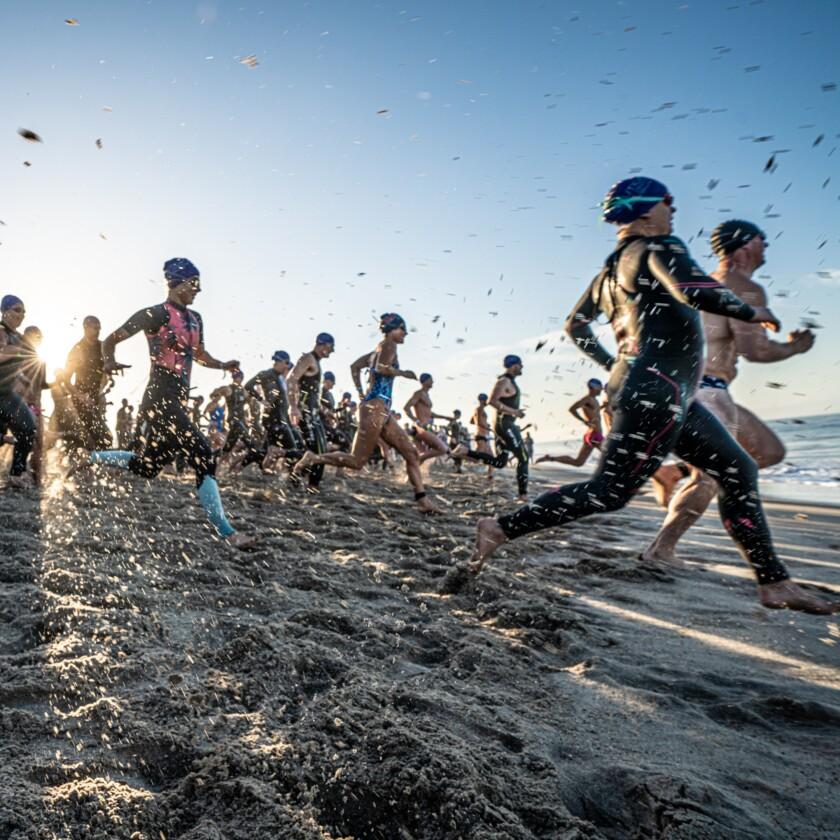 Swimmers in a triathlon running toward the ocean