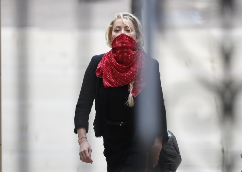 "Actress Amber Heard, center, arrives at the High Court in London, Monday, July 13, 2020. Johnny Depp is expected to wrap up his evidence at his libel trial against a tabloid newspaper that accused him of abusing ex-wife Amber Heard. The Hollywood star is suing News Group Newspapers, publisher of The Sun, and the paper's executive editor, Dan Wootton, over an April 2018 article that called him a ""wife-beater. (AP Photo/Alastair Grant)"