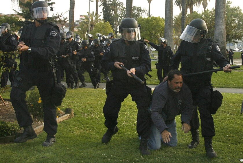 A Los Angeles police officer shoves a KCBS cameraman out of the way during a melee at MacArthur Park on May Day 2007.