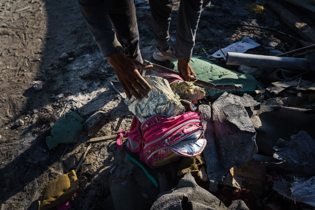 A child's pink school backpack in rubble