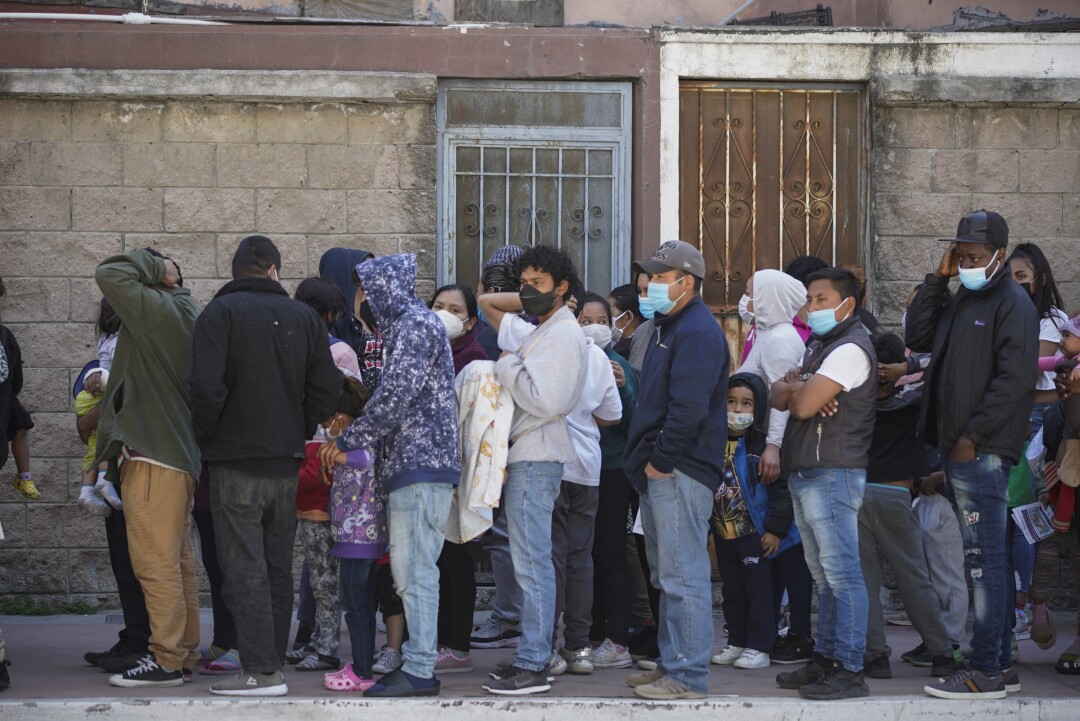 Asylum seekers wearing protective masks line up for food.