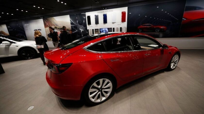 Buyers this month look over a Model 3 in a Tesla store in Cherry Creek Mall in Denver.