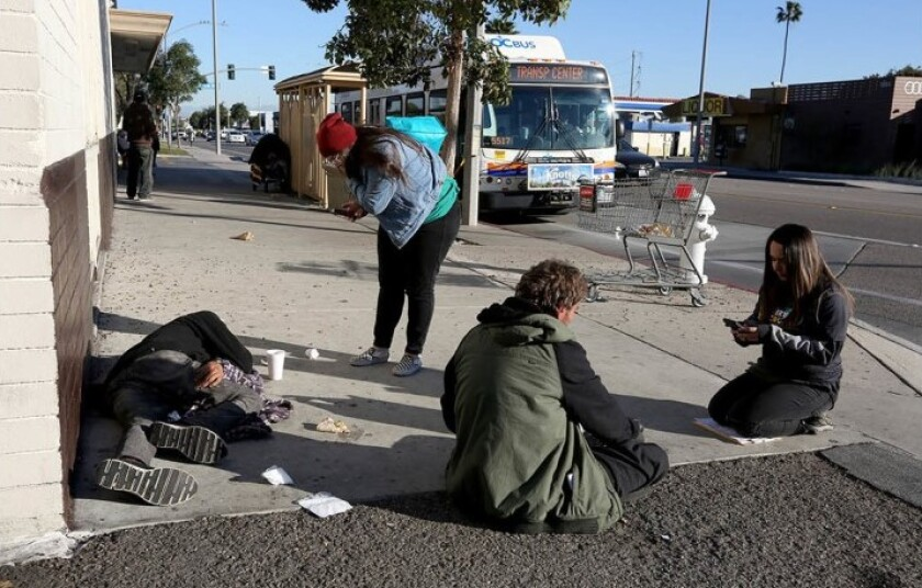 City Net volunteer and licensed vocational nurse Angie Munoz, left, and lead case manager Jennifer Munoz speak with homeless men in the 1800 block of Placentia Avenue in Costa Mesa during last January's Orange County Point in Time count.