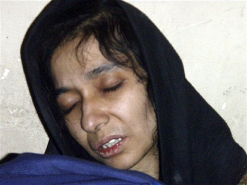 FILE - In this July 17, 2008 file photo, Aafia Siddiqui, possible al-Qaida associate is seen in the custody of Counter Terrorism Department of Ghazni province in Ghazni City, Afghanistan. In newly filed court documents, a psychologist disputes Siddiqui's claim that she was held captive overseas from 2008 to 2008. The American trained scientist is charged with shooting at U.S. soldiers and FBI agents in Afghanistan after her arrest as a suspected al-Quida operative. She was shot and wounded by U.S. Army officer after point a rifle at an Army Captain. ( (AP Photo/ File)