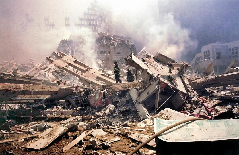 Firefighters walk amid the smouldering rubble of the World Trade Center