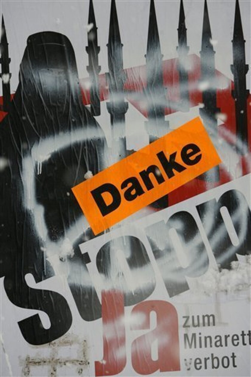 """A poster of a conservative initiative promoting the ban of the building of minarets in Switzerland is sprayed with a peace sign and a sticker saying """"thank you"""" in the village of Amsteg in central Switzerland, Monday, Nov. 30, 2009. Swiss voters overwhelmingly approved a constitutional ban on minar"""
