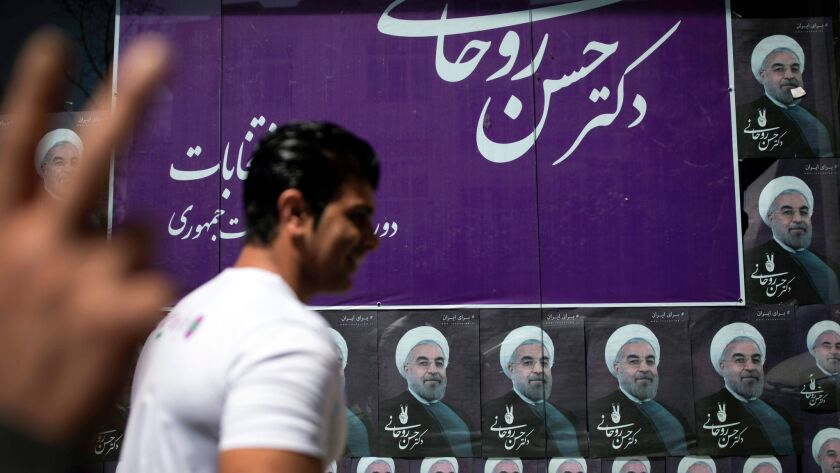 An Iranian man walks past portraits of President Hassan Rouhani outside his campaign headquarters in