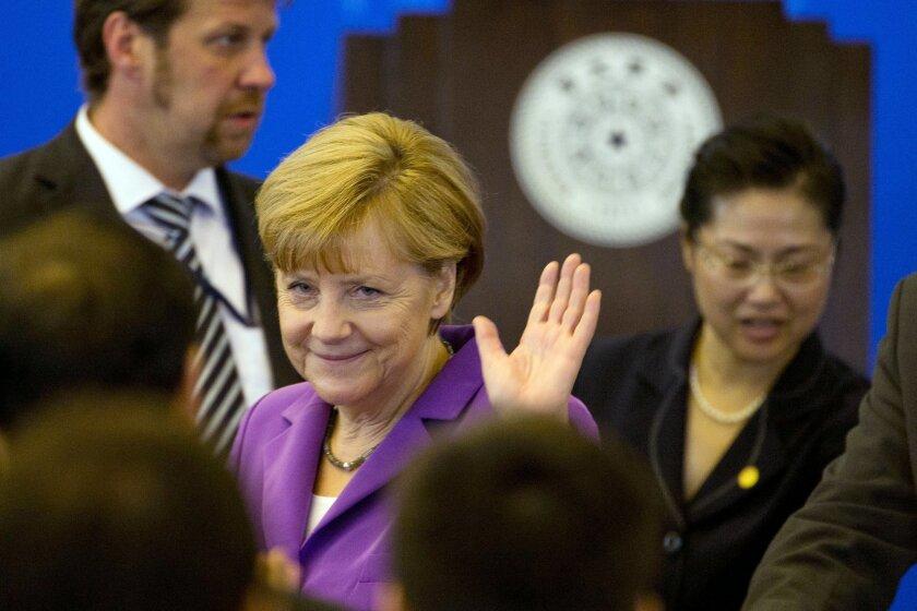 German Chancellor Angela Merkel waves upon arrival to deliver a speech at Tsinghua University in Beijing, China, Tuesday, July 8, 2014. (AP Photo/Ng Han Guan)