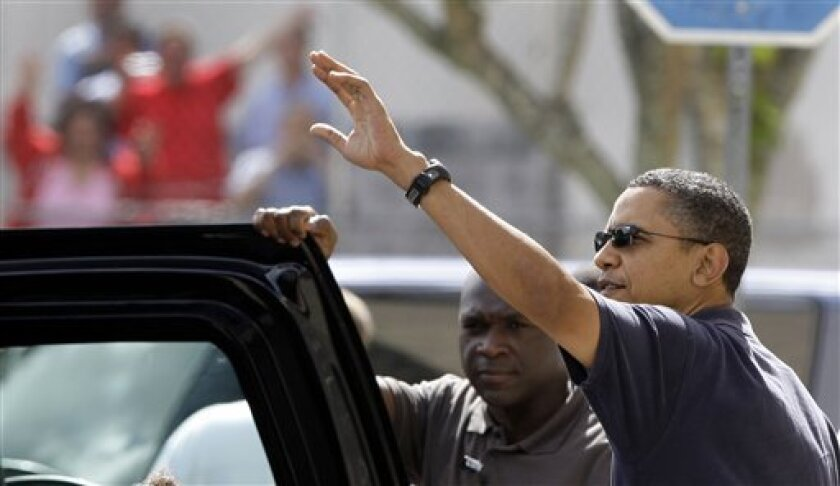 President Barack Obama, waves to the crowd after going to the movies in Kaneohe, Hawaii Thursday, Dec. 31, 2009. The Obamas are in Hawaii for the holidays.(AP Photo/Alex Brandon)