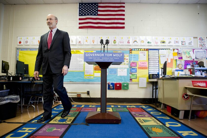 """ADVANCE FOR SUNDAY NOV. 1 - FILE - In this file photo taken Feb. 11, 2015, Pennsylvania Gov. Tom Wolf steps from the podium at the end of a news conference at Caln Elementary school in Thorndale, Pa., at the start of his statewide """"Schools that Teach Tour"""" to promote the governor's education fundin"""