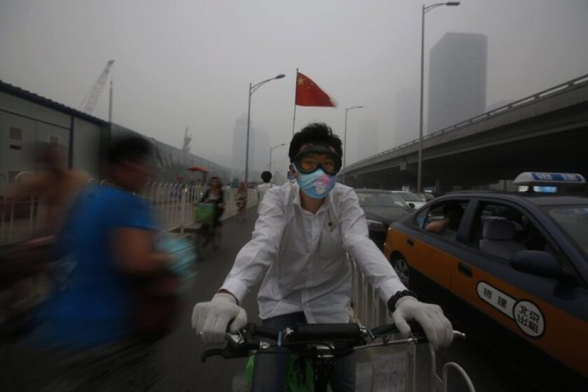 A man wears a mask as he bicycles through smog-shrouded Beijing.