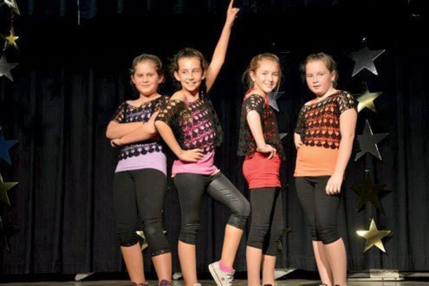 Fourth-graders Kate MacDonald, Ruaida Alkafaji, Ahna Wittkow and Terra Evans take a bow after their dance number. (Courtesy Photos)