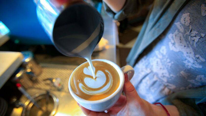 Lindsey Vargo assistant manager at the Bird Rock Coffee Roasters in Little Italy pours a latte artwork created from the steam milk for a customer.