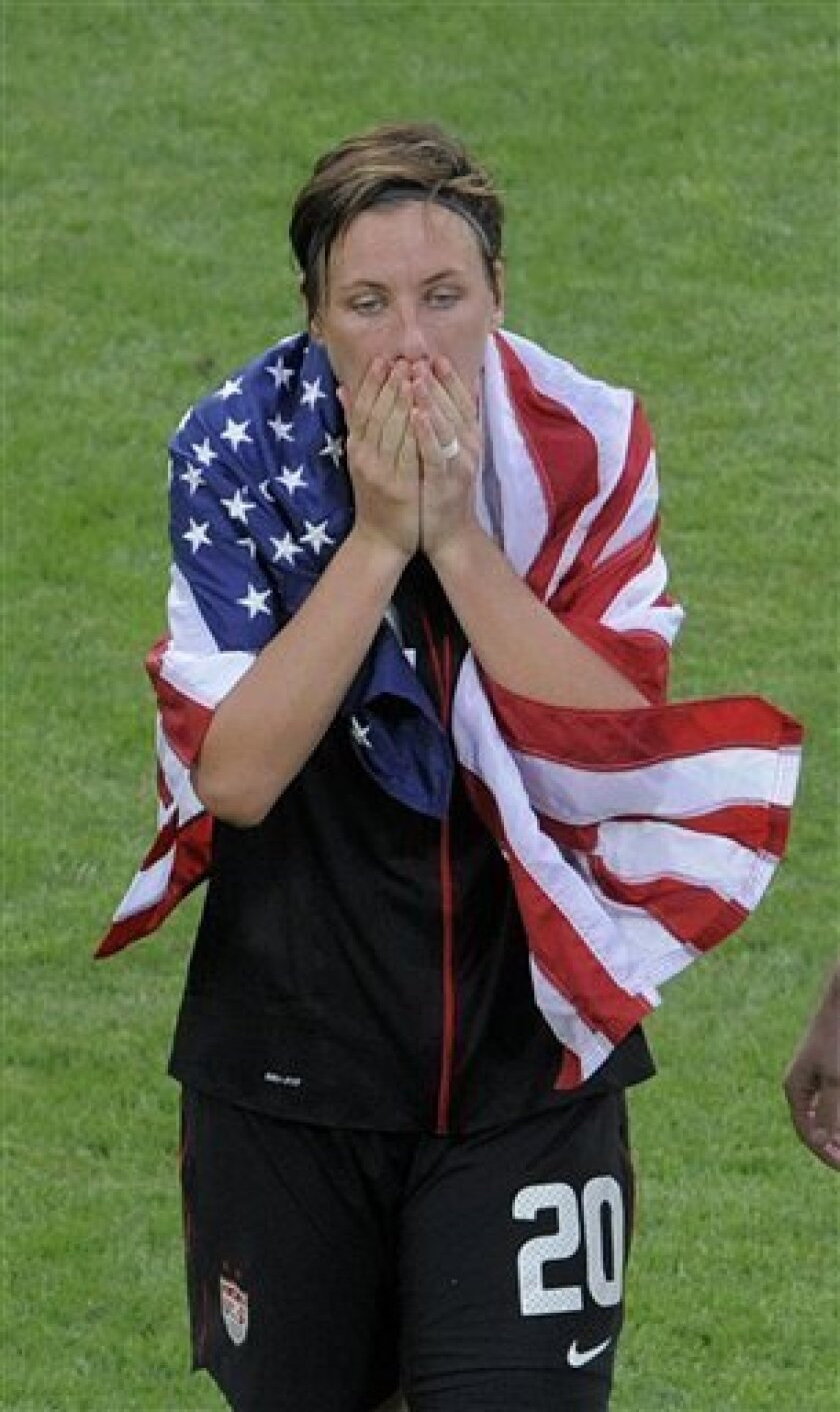 United States' Abby Wambach is wrapped in a US flag after her team won in a penalty shootout the quarterfinal match between Brazil and the United States at the Womenís Soccer World Cup in Dresden, Germany, Sunday, July 10, 2011. (AP Photo/Jens Meyer)