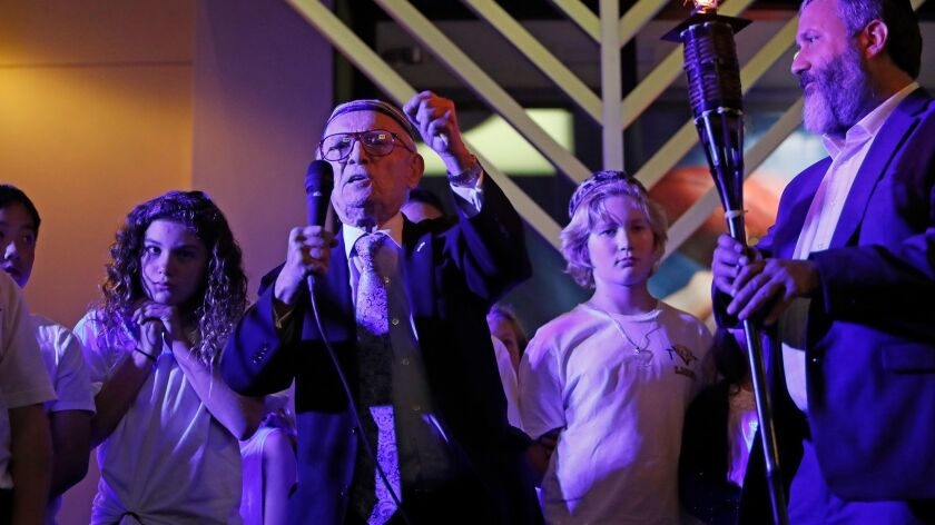 Keynote speaker Dr. Jacob Eisenbach, left, a 93-year-old Holocaust survivor, talks during the menorah lighting ceremony celebrating the first night of Hanukkah at Fashion Island on Tuesday in Newport Beach. At right is Rabbi Reuven Mintz with the Chabad Center for Jewish Life.