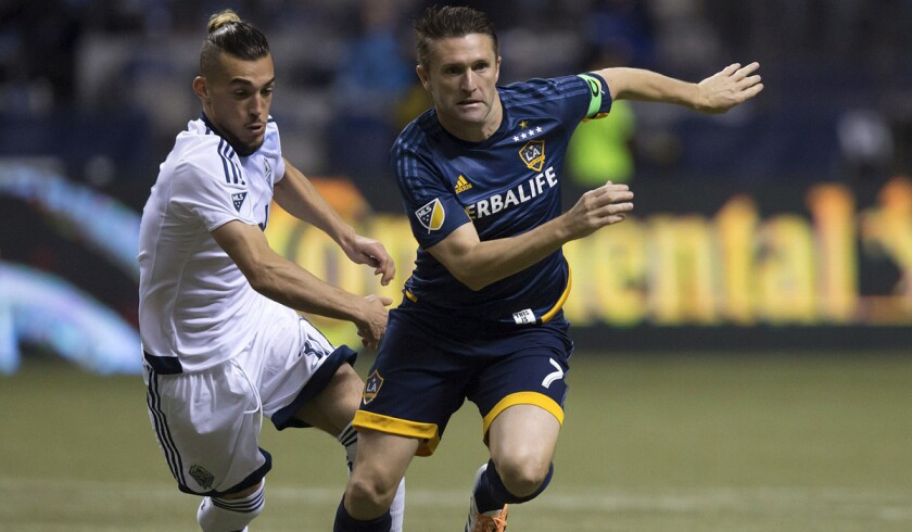 Los Angeles Galaxy's Robbie Keane tries to get away from Vancouver Whitecaps' Russell Teibert during the Galaxy's 2-0 loss to the Whitecaps.