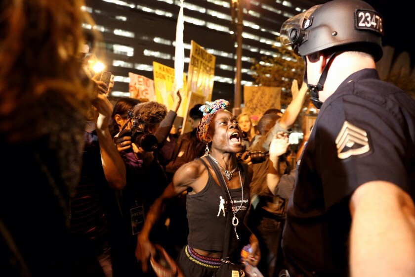 LOS ANGELES, CA. -- TUESDAY, NOVEMBER 25, 2014: Protesters confront police officers outside LAPDHQ i
