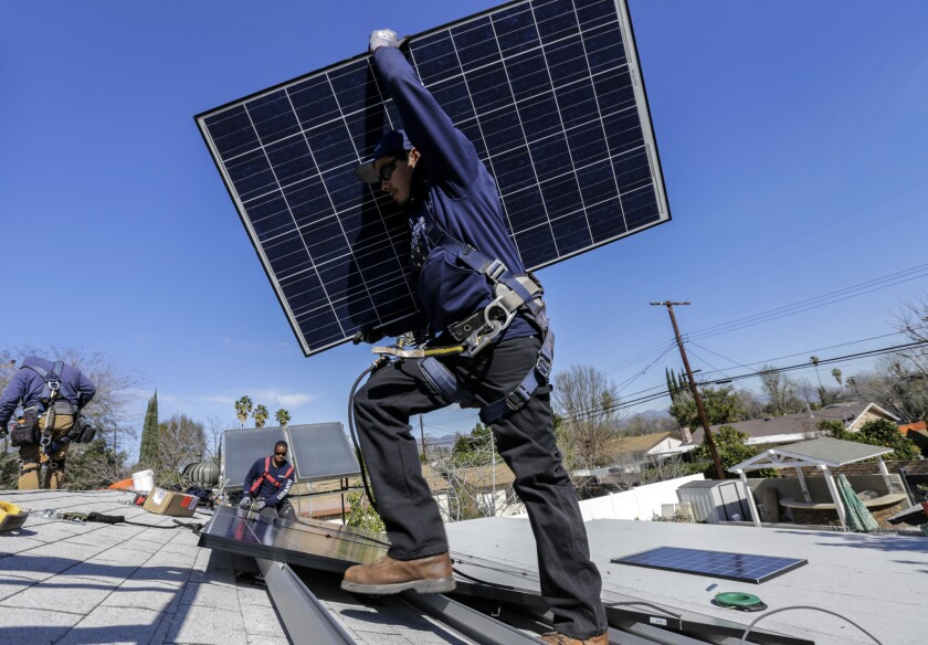 Alejandro DeLeon carries a solar panel for Sunrun home solar company instal a solar system on home in Van Nuys.