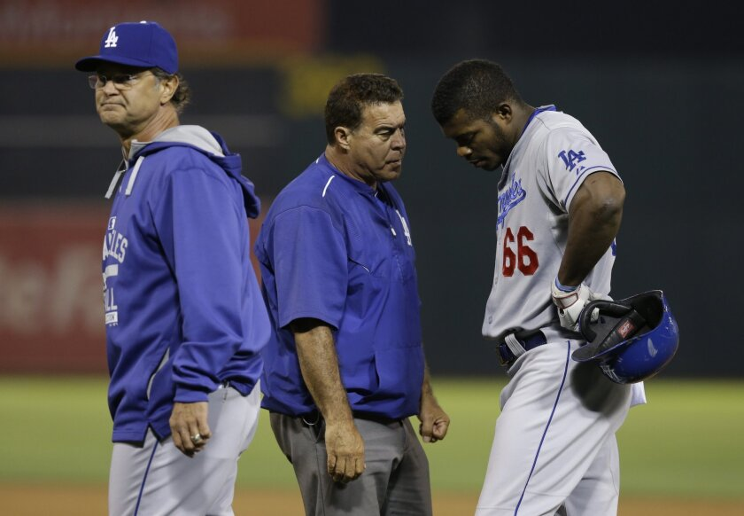 Yasiel Puig speaks with trainer Stan Conte in the eighth inning against Oakland on Tuesday night.