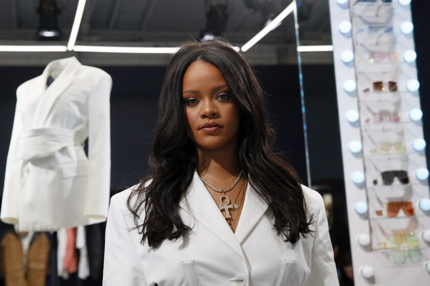 Rihanna posing in a white suit and cross necklace.
