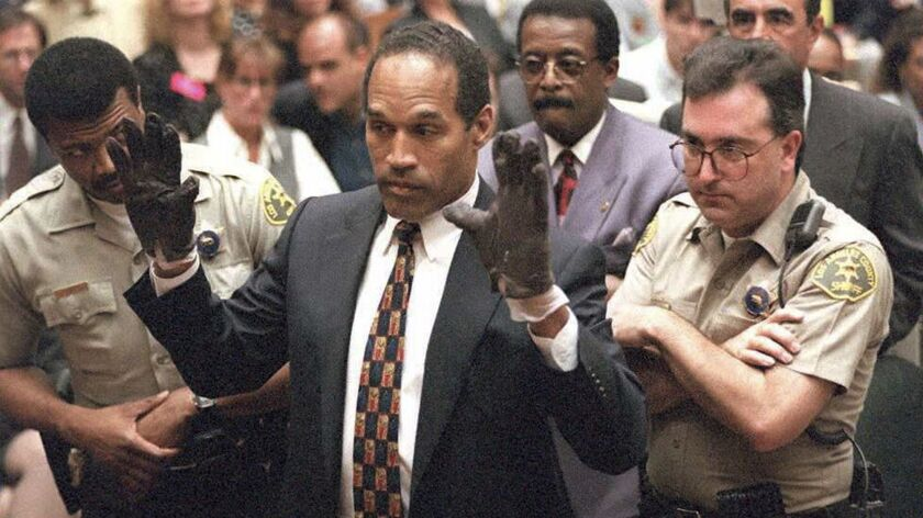 O.J. Simpson holds up his hands for the jury on June 14, 1995, while wearing the bloody gloves found