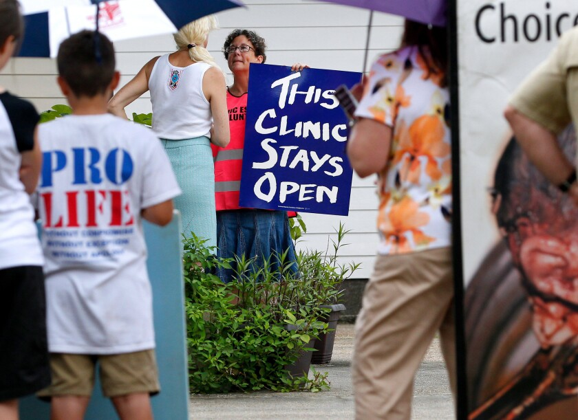 """In front of pro-life activists, a volunteer guards the entrance of the Causeway Medical Clinic in Metairie, La., with a sign reading, """"This Clinic Stays Open."""""""