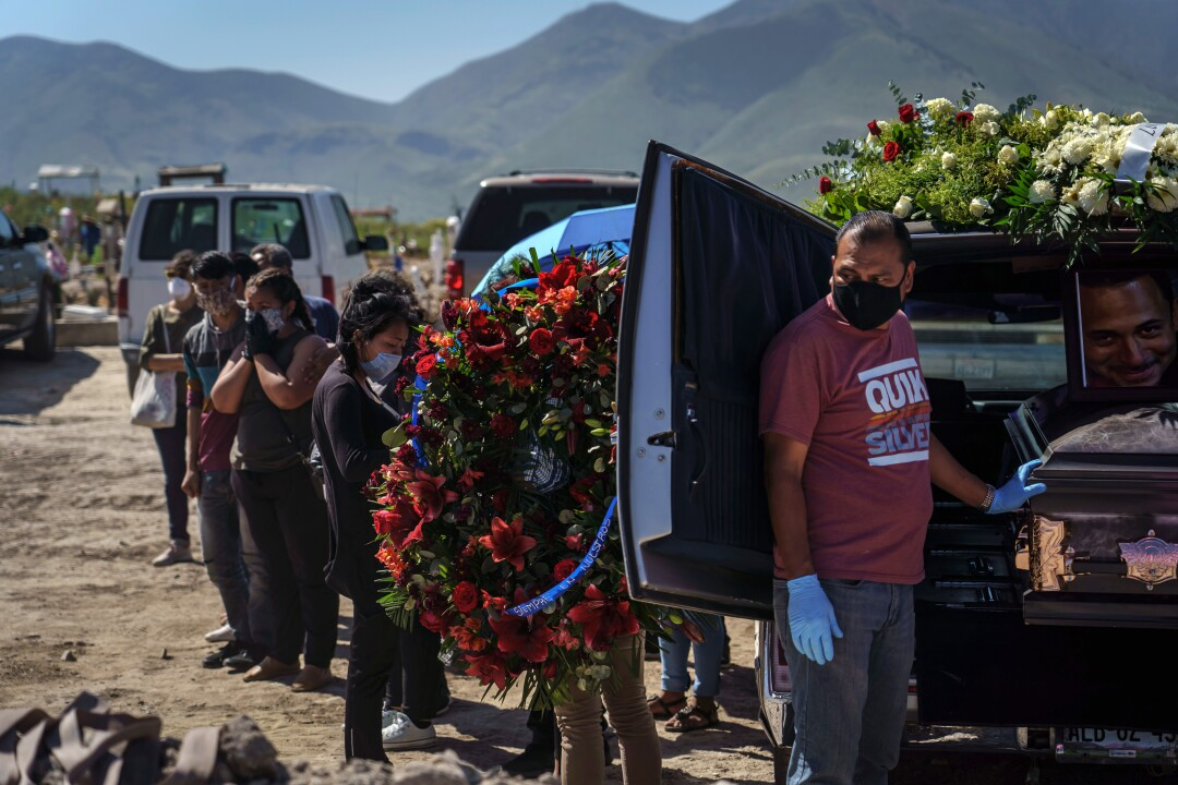 A funeral home worker prepares to unload a casket for cemetery workers to transfer into a grave as family members of the deceased stand nearby.