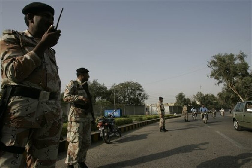 Soldiers of Pakistan paramilitary force stand alert at a roadside as security enhanced in Karachi, Pakistan on Monday, March 8, 2010. The American-born spokesman for al-Qaida has been arrested by Pakistani intelligence officers in the southern city of Karachi, two officers and a government official said Sunday as video emerged of him urging U.S. Muslims to attack their own country. (AP Photo/Shakil Adil)