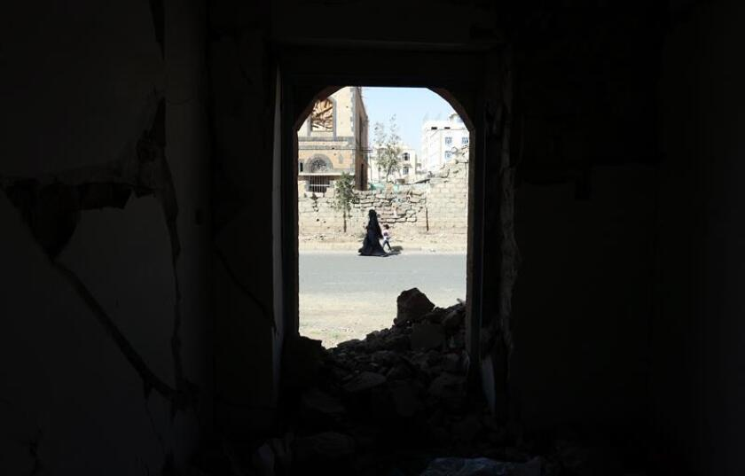 A Yemeni woman and her child walk past a destroyed building allegedly targeted by a previous Saudi-led airstrike, in Sana'a, Yemen, 04 February 2019. According to reports, representatives of the Saudi-backed Government of Yemen and the Houthi rebels are scheduled to hold talks 05 February in Jordan over a UN-brokered prisoner swap involving more than 15 thousand war prisoners and forcibly detained people allegedly captured in the nearly four-year conflict. EPA-EFE/YAHYA ARHAB