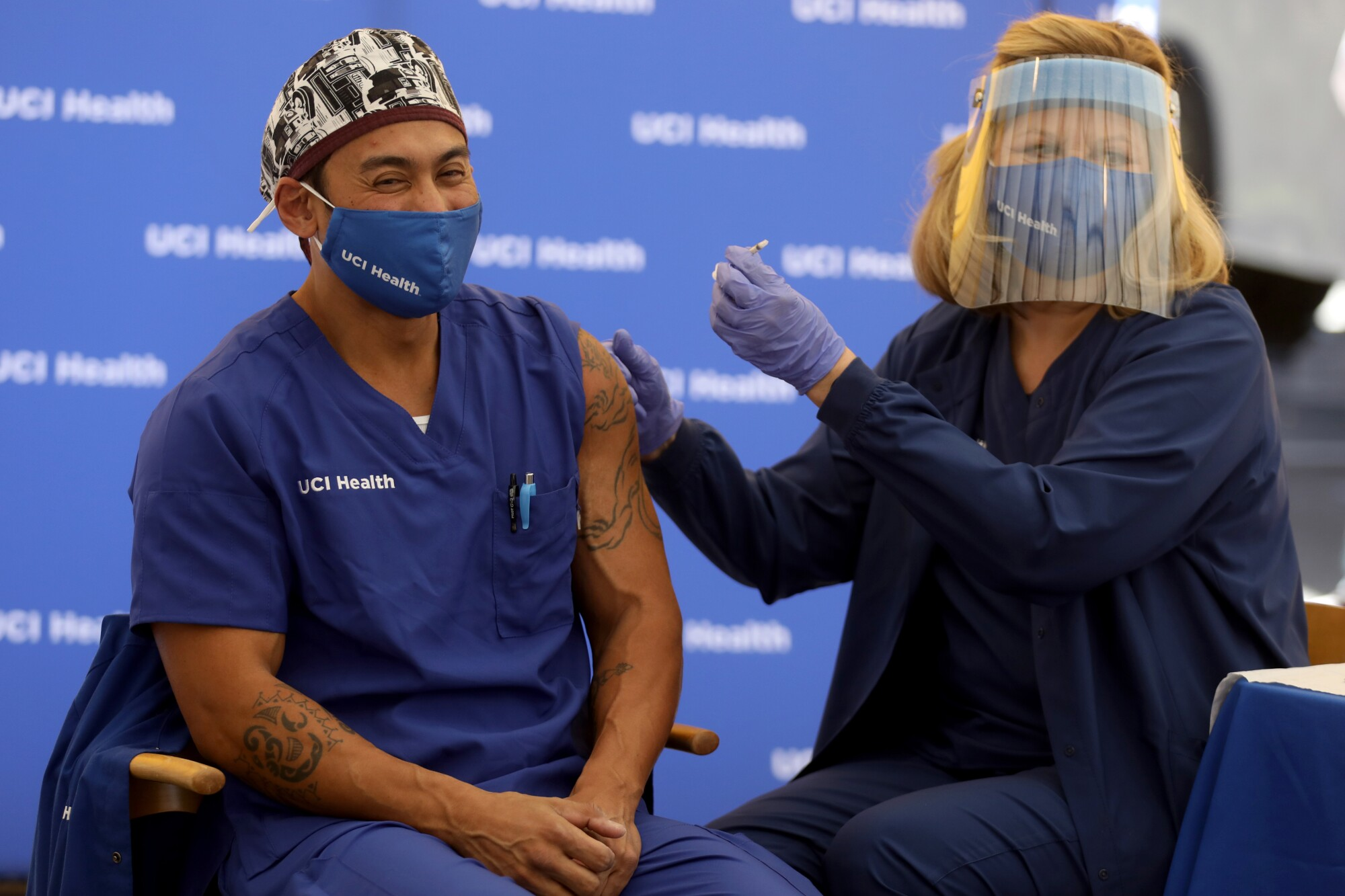 A healthcare worker dressed in scrubs receives a vaccine administered by a nurse wearing a face shield