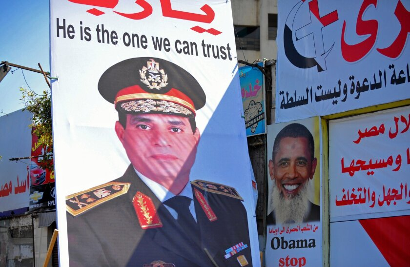 Posters in Cairo show Egypt's army chief General Abdel Fattah Sisi, left, and President Obama with a beard and bearing a slogan referring to the belief by some Egyptians that the U.S. supports the Muslim Brotherhood and the country's ousted president Mohamed Morsi.