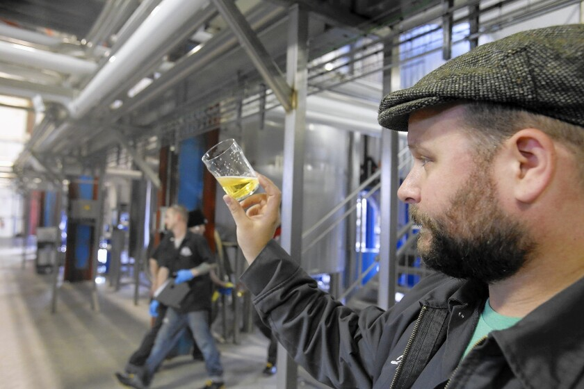 Brewer John Dunne checks a lager beer at Golden Road Brewing in Atwater. Owner Tony Yanow is expanding his business in Glendale rather than Los Angeles.