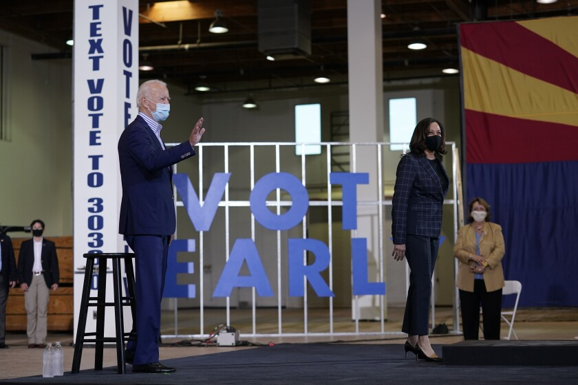 "Joe Biden and Kamala Harris stand in front of a ""vote early"" sign in Phoenix."