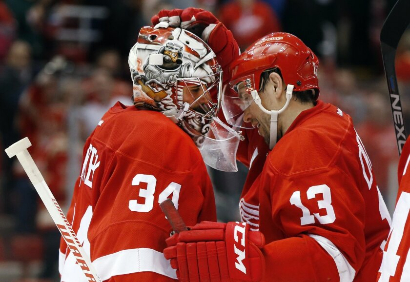 Detroit Red Wings goalie Petr Mrazek (34) and Pavel Datsyuk (13) celebrate their 3-0 win over the Florida Panthers after an NHL hockey game, Monday, Feb. 8, 2016 in Detroit.  (AP Photo/Paul Sancya)